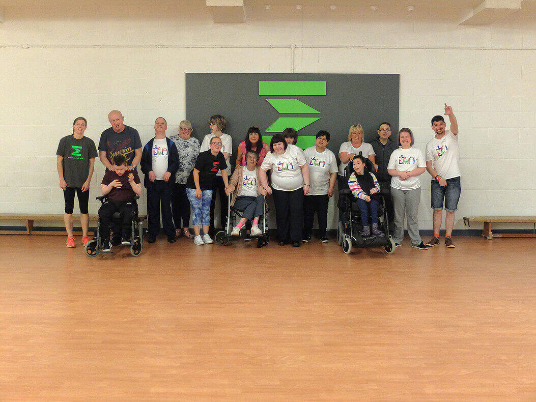 A happy group of varying ages and abilities gather in a bright gym, including three people using wheelchairs.