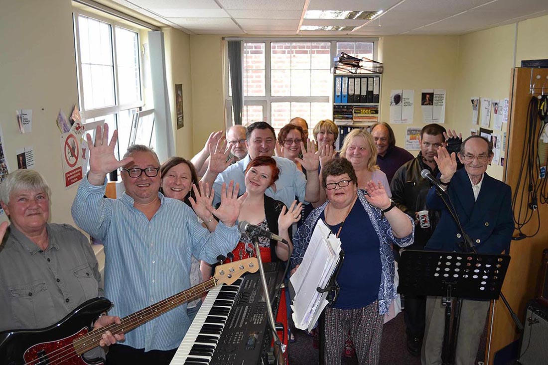 A group of middle-aged and elderly adults standing close together hold instruments and wave towards the camera!