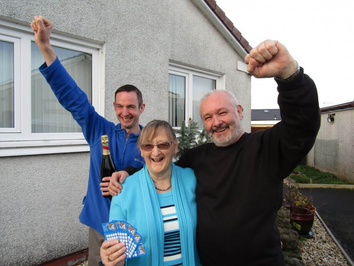 A retirement age couple and their adult son pump their fists in the air, while one holds up five scratch cards.