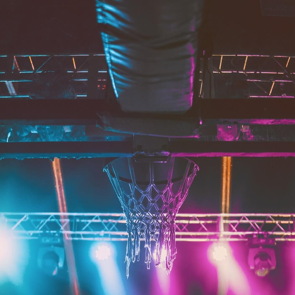 A view of a basketball hoop from underneath, lit in neon blue and magenta.