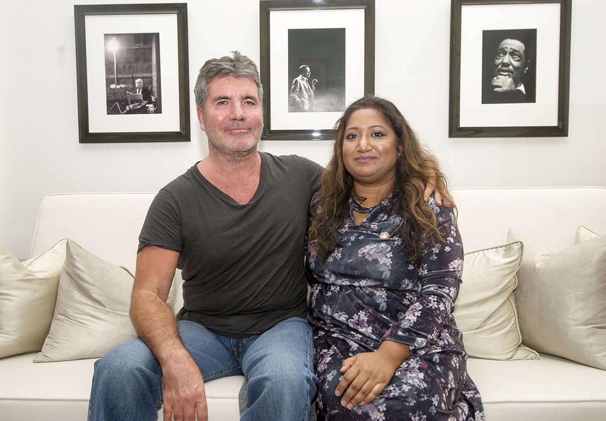 Simon Cowell, a middle-aged man with grey hair, sits on a white couch with his arm around a woman in a floral dress.