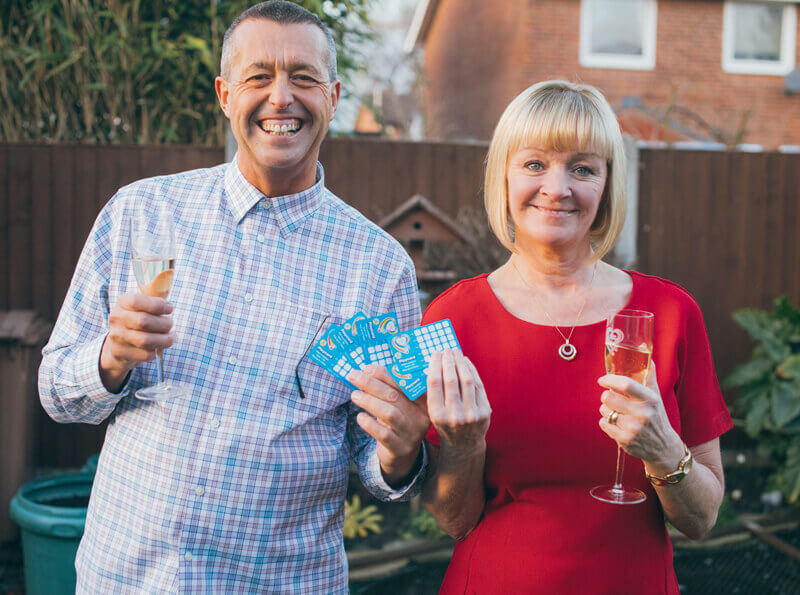 A smiling middle-aged couple hold up five scratch cards between them while they raise champagne glasses in a toast.