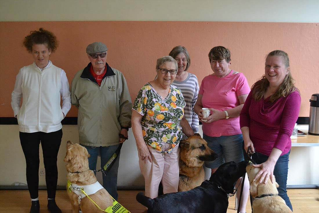 Six people stand together, accompanied by four happy service dogs.