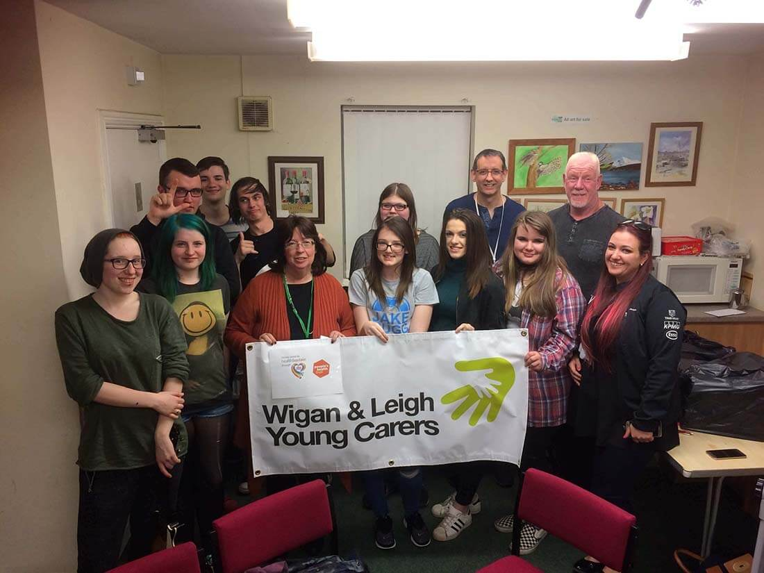 "A diverse group of people stand together in a community center, holding up a banner that read, ""Wigan & Leigh Young Carers""."