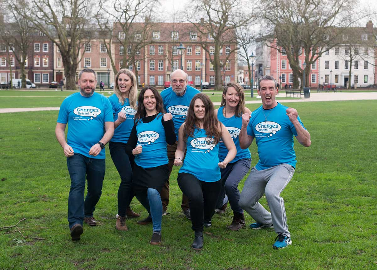 A group of seven adults of varying ages strike a silly pose on a field while wearing matching bright blue shirts.