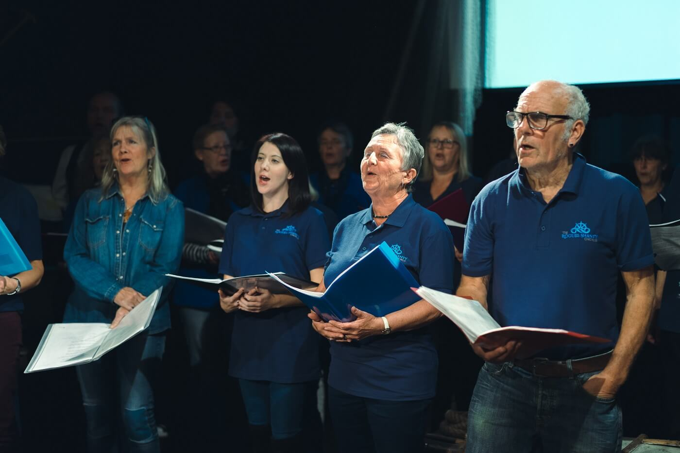 A large group of people in matching dark blue polos stand and sing while holding music booklets.