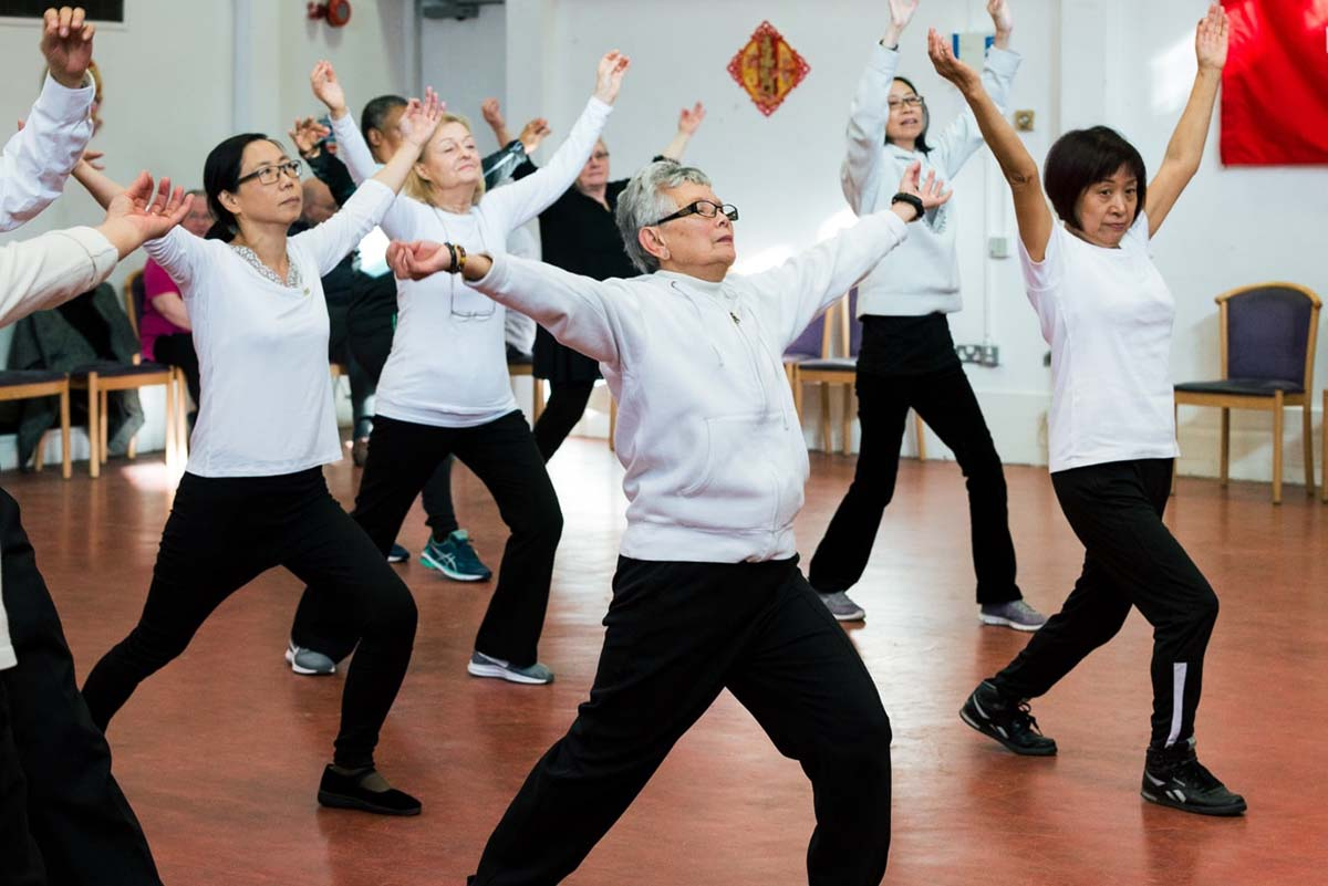 A group of middle aged and elderly women wearing matching work-out clothing perform a tai chi lunge in unison.