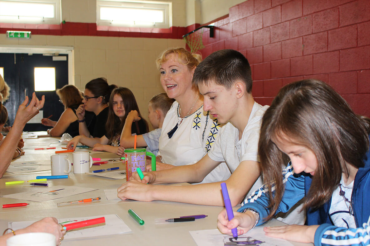 A blonde women sits at a table full of children drawing with magic markers on sheets of paper in a gym.