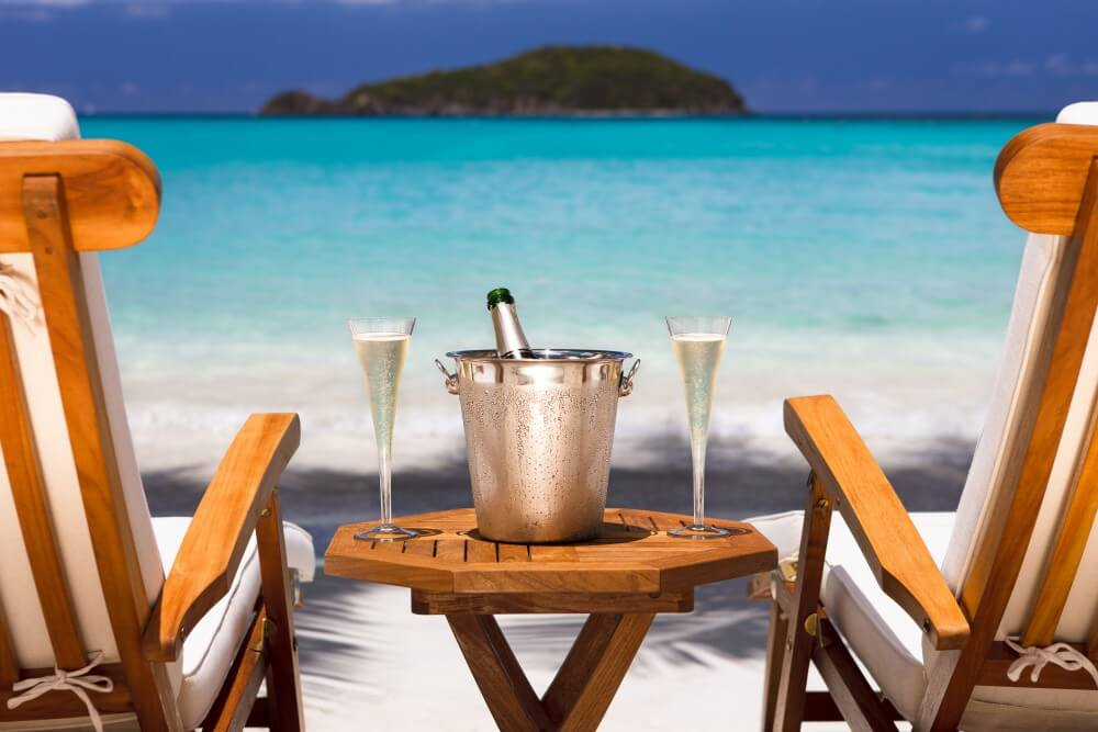 A chilled bottle of champagne and two glasses rest on a table between two beach chairs overlooking the ocean.