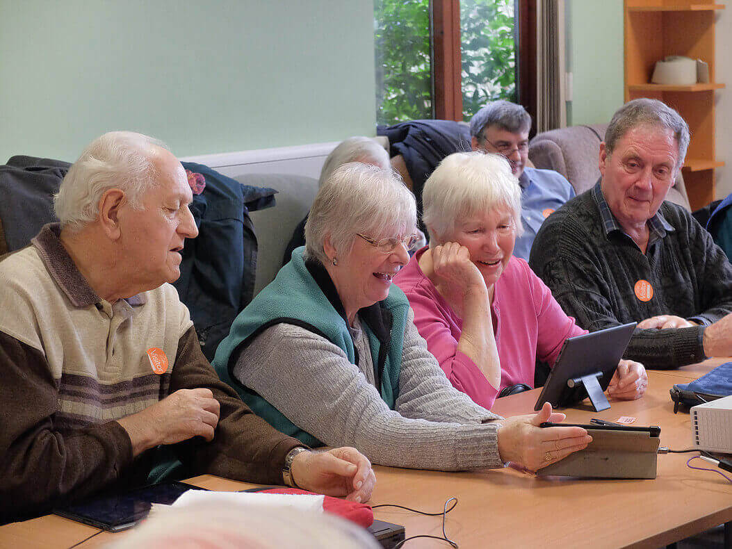 Four senior citizens sit at a long table, looking at tablet computers in front of them.