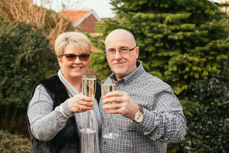 A  couple of retirement age standing outdoors smile and raise full champagne glasses towards the camera.