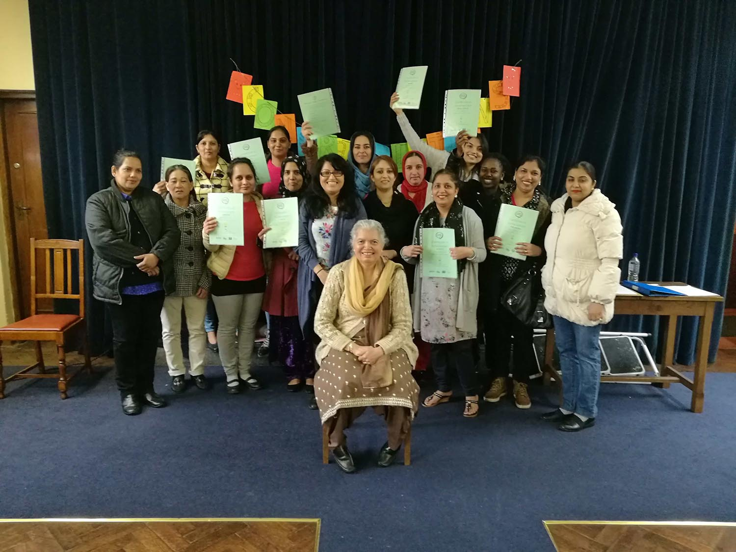 An ethnically diverse group of women standing together, proudly holding up green pieces of paper.
