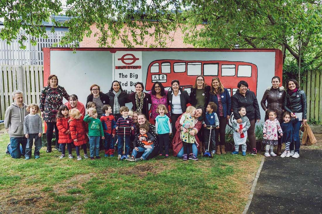 """A large group of parents and their young children stand in front of a large mural that reads, """"The Big Red Bus Club""""."""