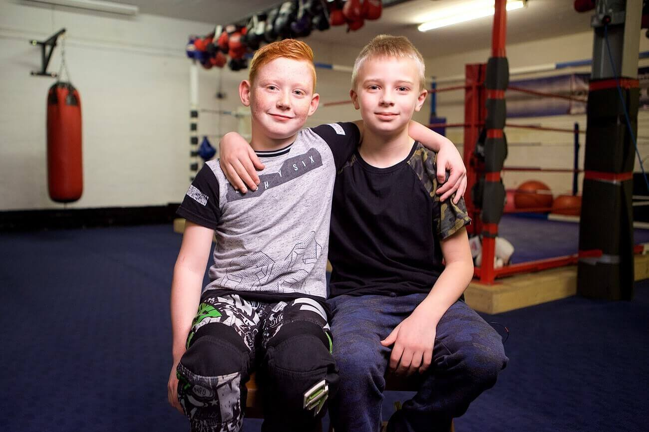 Two young boys, one blonde and one redhead, sit with their arms around each other in front of a boxing ring.
