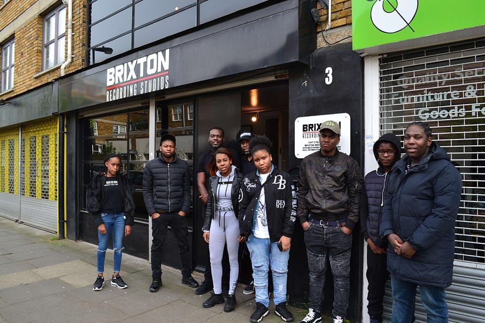 A smiling group of nine Black young people in stylish clothes stand in front of Brixton Recording Studios.