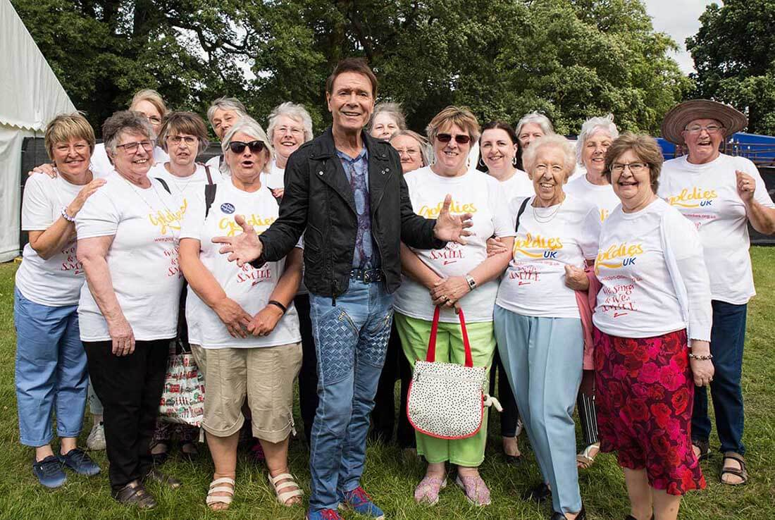 "A smiling man wearing a stylish black jacket and jeans stands with a group of older women wearing matching ""Goldies"" tees."