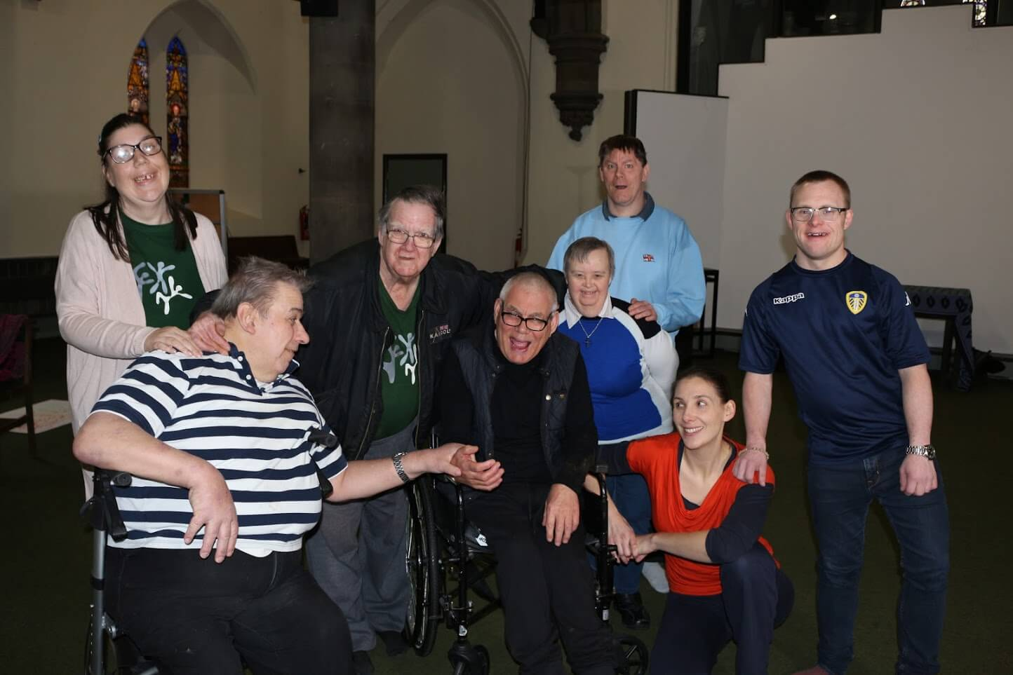 A group of people of varying ages and disabilities stand together inside a church and smile for the camera.