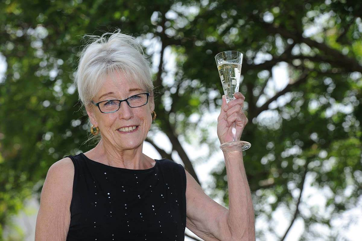 A smiling elderly white woman with white hair and glasses in a black evening dress holds up a champagne flute.