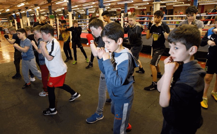 A group of young boys stand in two lines in a boxing gym, with their fists raised in a self-defense posture.