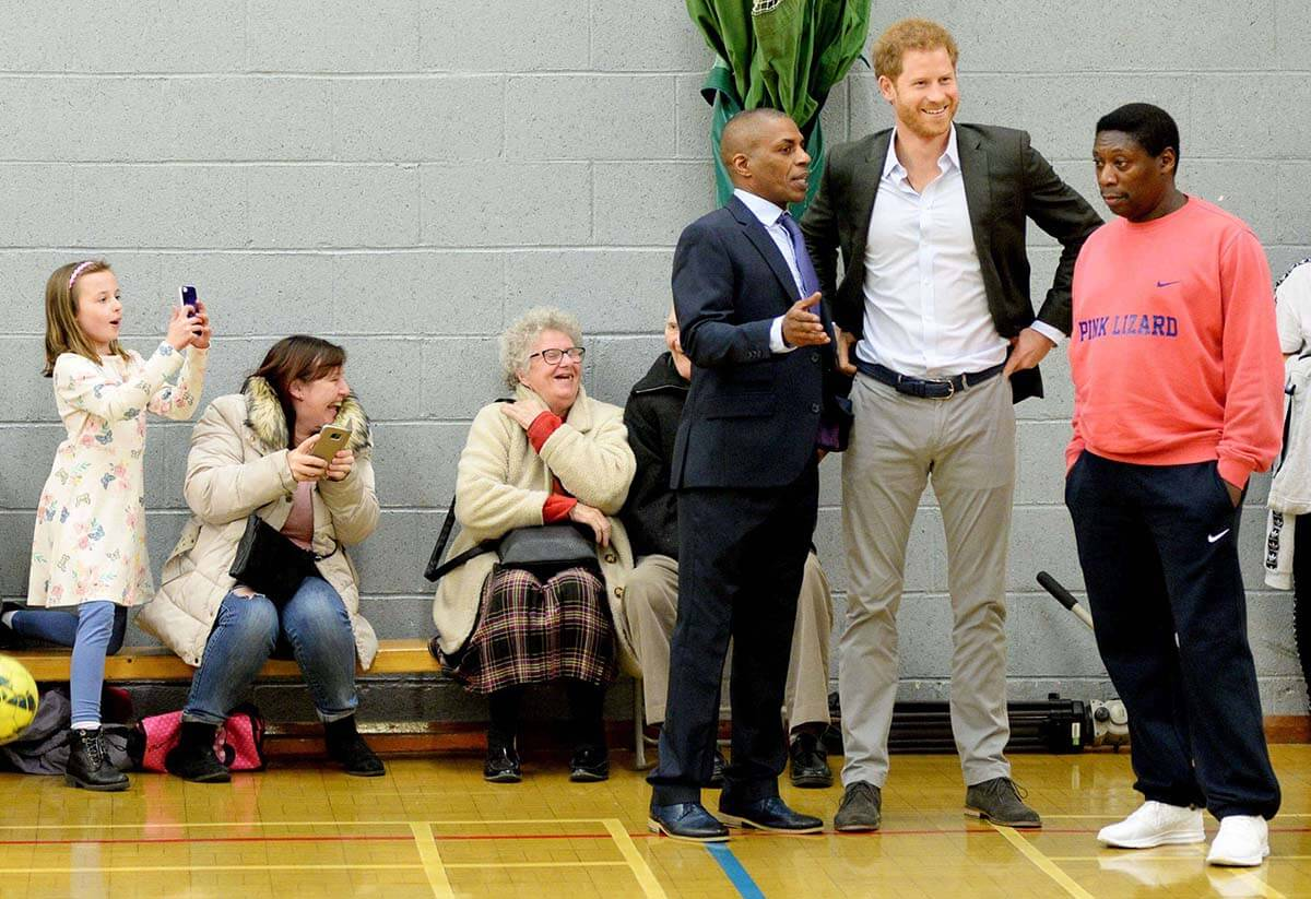 Prince Harry, a tall redheard in casual business clothes, chats with people standing on the sideline of a basketball court.
