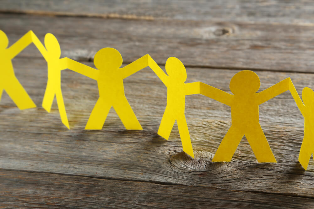 A cut-out paper chain in the shape of people stretches across a wooden table surface. Learn about monthly charity lottery