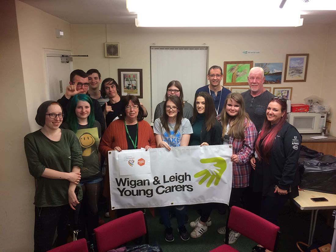 """A diverse group of people stand together in a community center, holding up a banner that read, """"Wigan & Leigh Young Carers""""."""