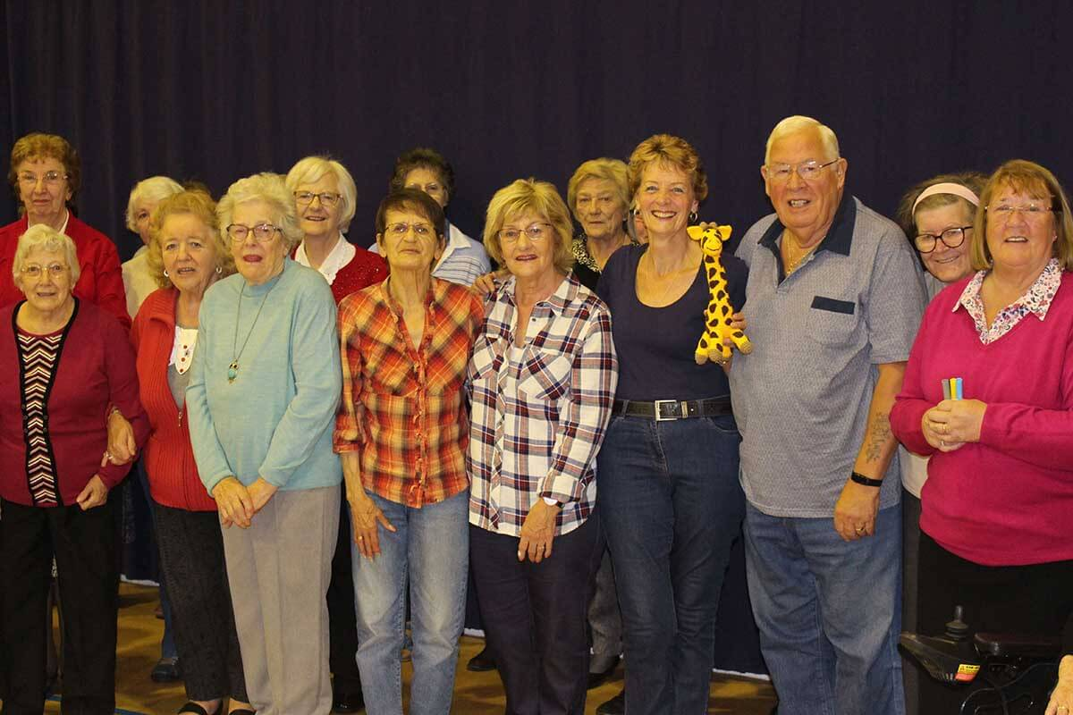 A large group of smiling senior citizens stand in front of a dark blue stage curtain.