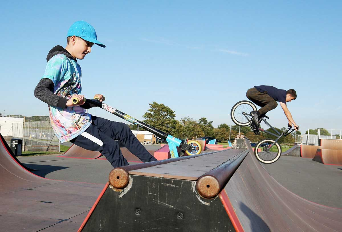 Two boys ride a bike and a scooter over a ramp in an outdoor skate park.