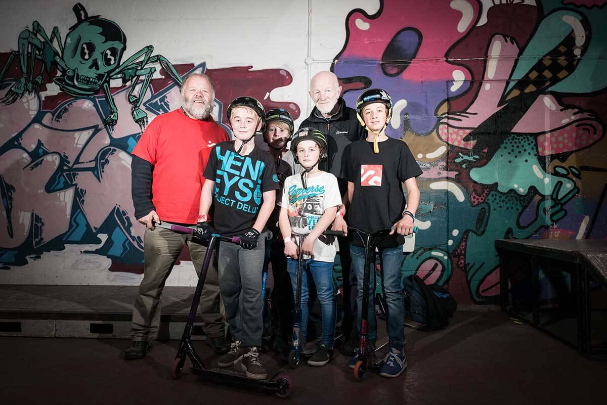 A group of four young boys on scooters stand with two older men in front of a large graffiti wall mural.