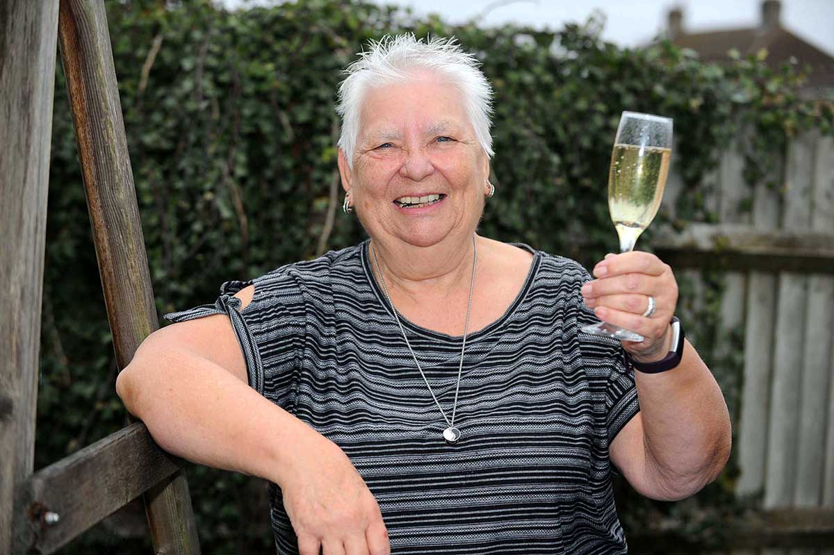 A smiling elderly woman with short white hair leans against a wooden pole, holding up a champagne glass.