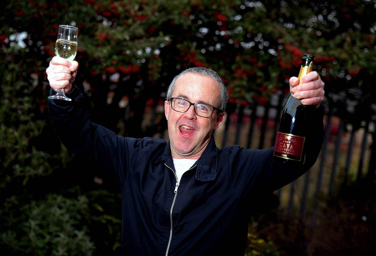 A jubliant man with glasses in a dark blue windbreaker holds up a champagne bottle in one hand and a glass in the other.