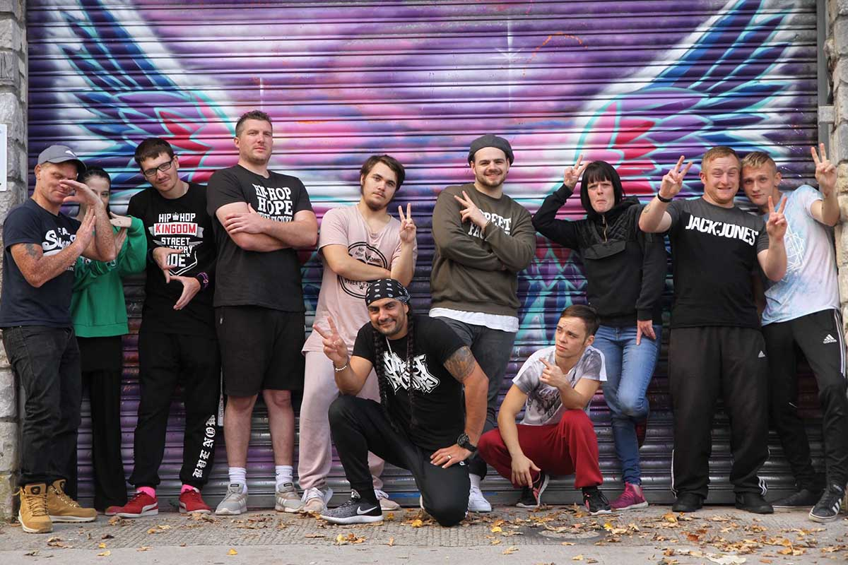 A group of young adults in trendy clothes throw up peace signs in front of a large graffiti mural.