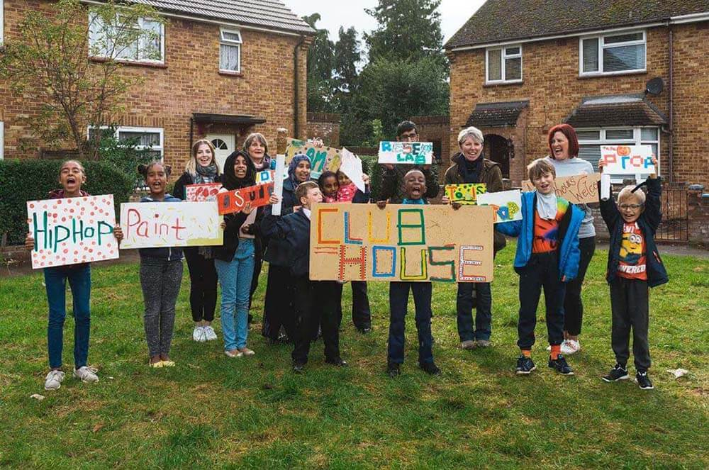 "A diverse, cheering group of children hold up signs that read, ""Club House"", ""Hip Hop"" and ""Paint""."