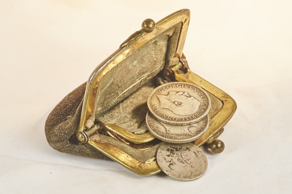 Old victorian purse on ground with some coins falling out