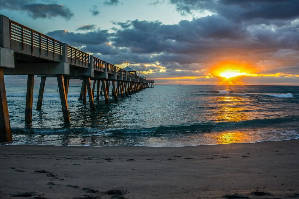 The sun sets in a cloudy sky over a beautiful beach, with a long pier on the left.