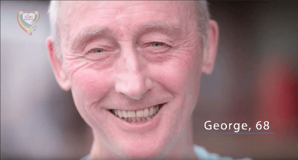 Close-up photo of a man's face. He has blue eyes, wrinkles, and a big smile. | George, 68