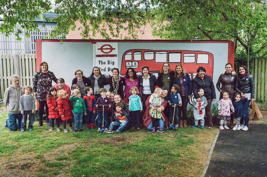 "A large group of parents and their young children stand in front of a large mural that reads, ""The Big Red Bus Club""."