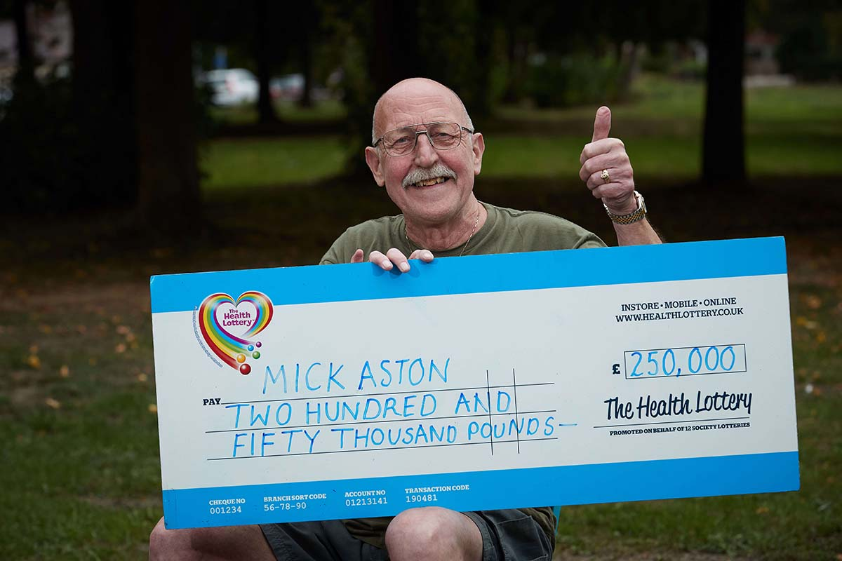 Mick  holds up a Health Lottery giant check for £250,000