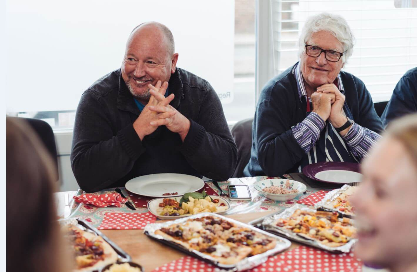 Two older white men sit at a colorful table laid with food, their hands clasped by their faces.