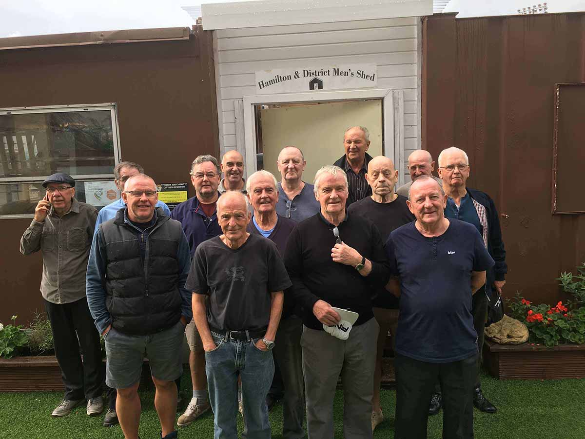 """A smiling group of elderly men stand together in front of a building with a sign reading, """"Hamilton & District Men's Shed""""."""